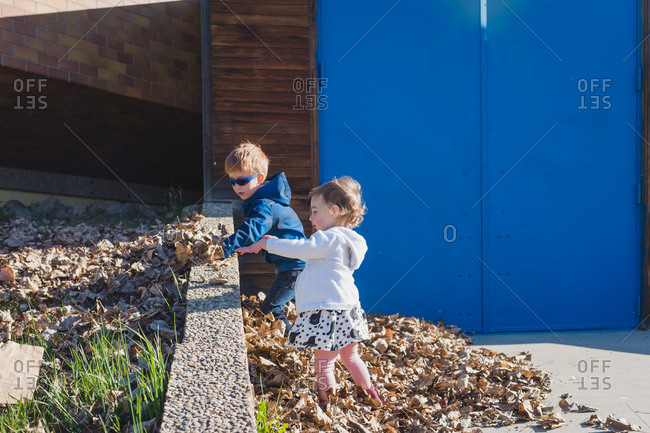 Two children playing outside in a leaf pile
