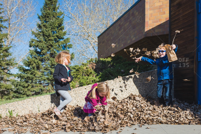 Three children playing outside in a leaf pile