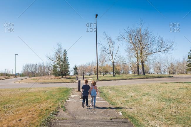Boy and girl walk hand-in-hand outside on a sidewalk