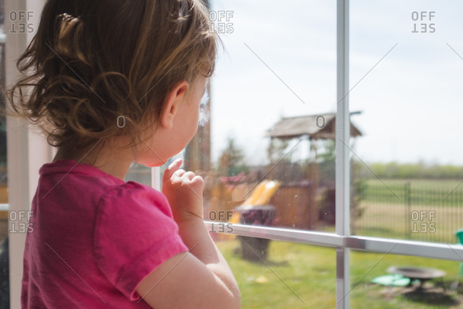 Young girl looking out a window at a play structure in her backyard