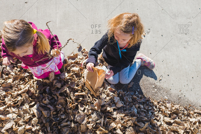 Children playing outside in a leaf pile