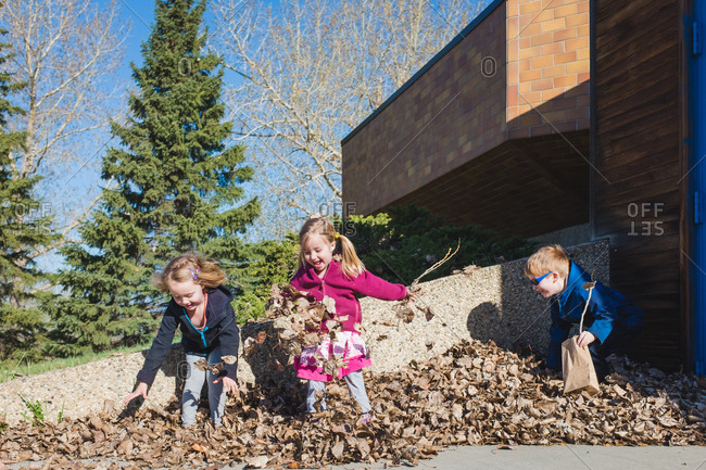 Children playing outside in a leaf pile on the driveway