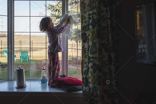 Young girl standing on a window seat washing a window