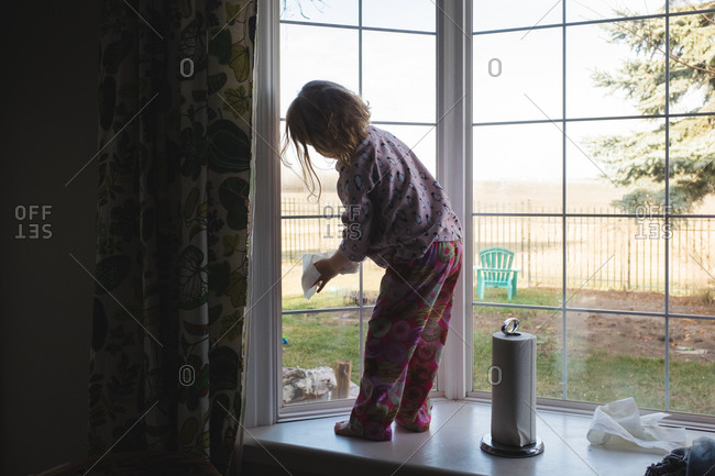 Young girl standing on a window ledge washing a window