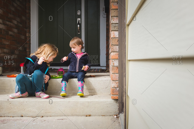 Two girls sitting on the porch together having a snack