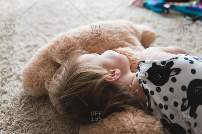 Young girl lying down on the floor with her stuffed toy animal