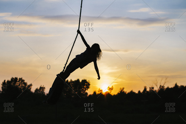 Silhouette of a girl on a rope swing