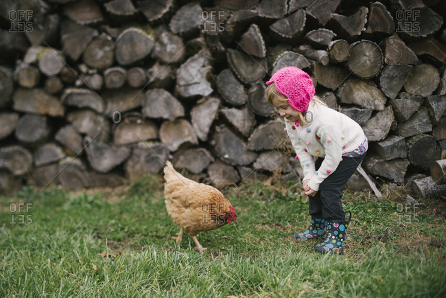 Girl outside looking at a hen