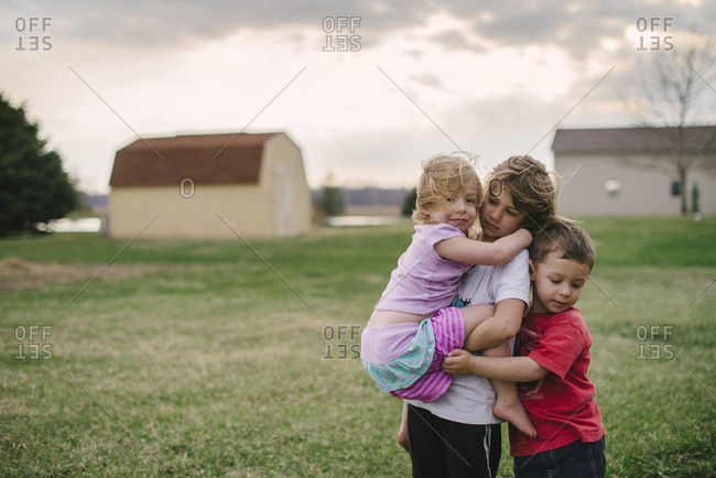 Portrait of three children standing outside on a windy day