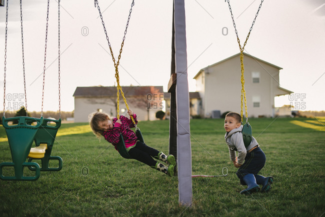 Boy and girl swinging together in their backyard