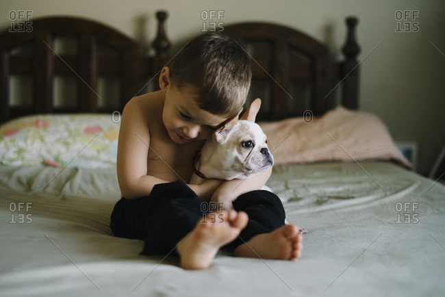Boy sitting on a bed holding a French Bulldog