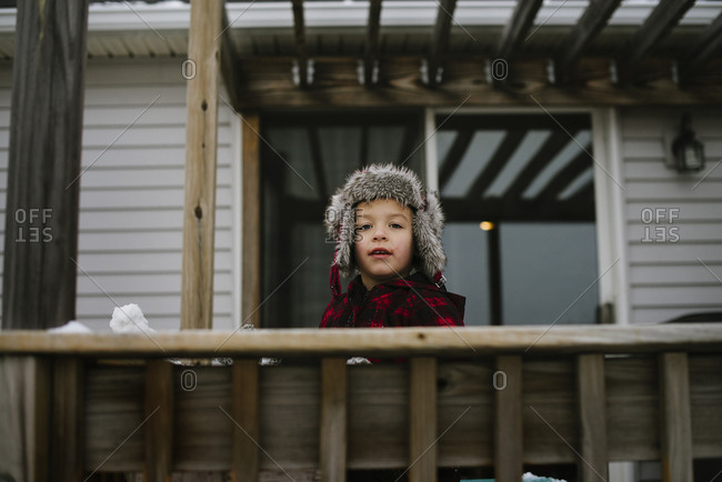 Boy wearing a fur hat and coat looking out over the edge of a wood deck