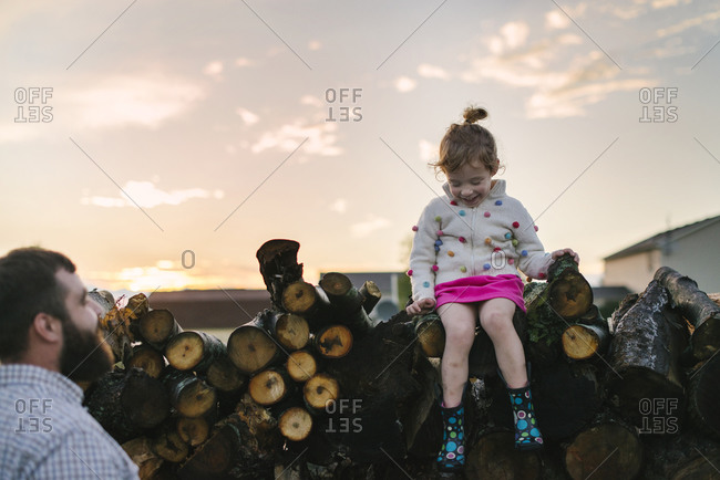 Girl sitting on a wood pile next to her father