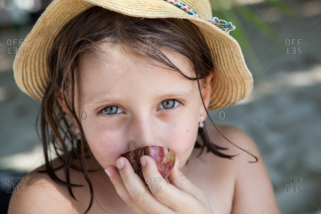 Portrait of a girl eating a passion fruit in Thailand