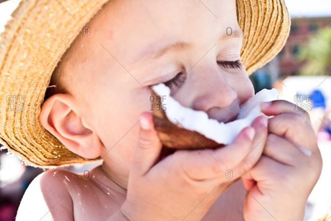 Portrait of a little boy eating a coconut