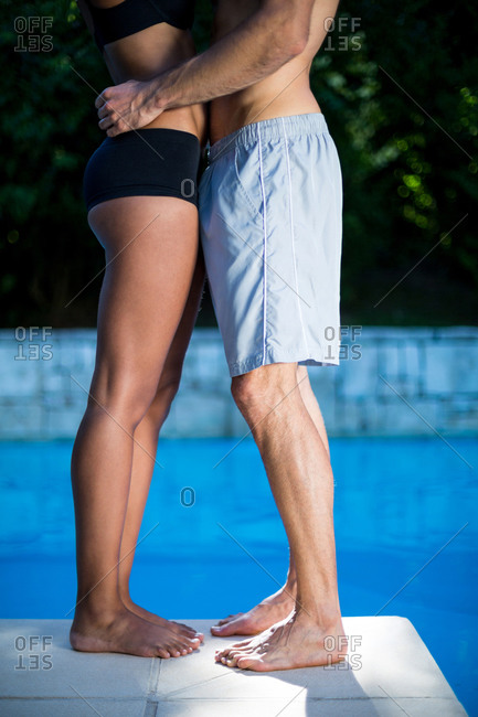Mid section of couple standing near swimming pool