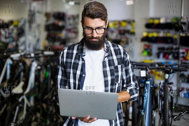 Bike mechanic checking laptop in bike repair shop