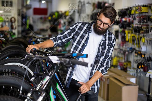 Bike mechanic checking bicycles in bike repair shop