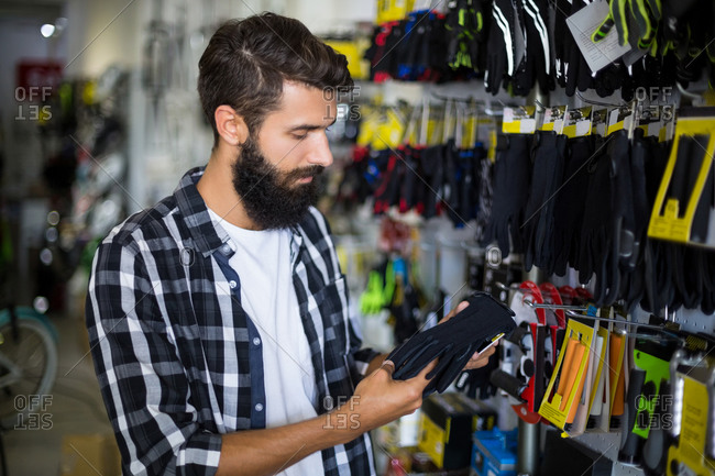 Serious customer picking out gloves in bike repair shop