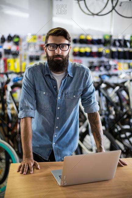 Bike mechanic checking at laptop in bike repair shop