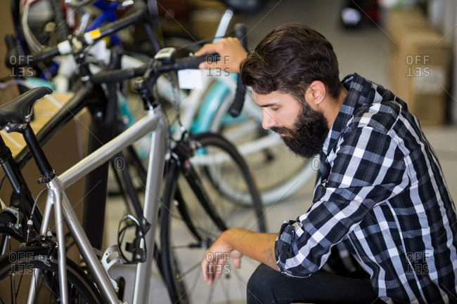 Bike mechanic checking on a bicycle in bike repair shop