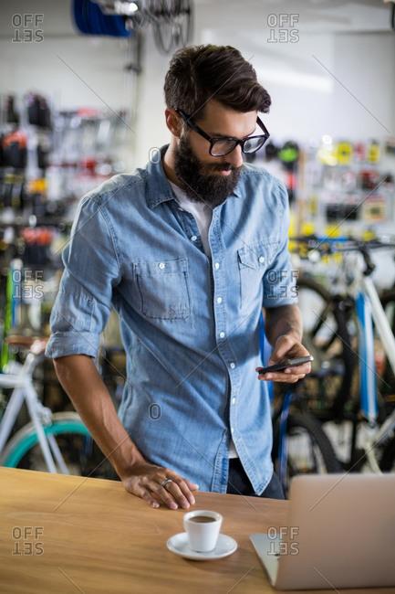 Bike mechanic checking at smartphone and having coffee in bike repair shop