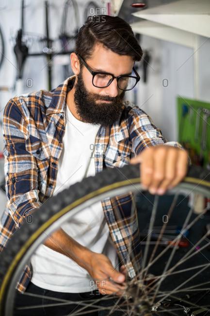 Bike mechanic checking at bicycle in bike repair shop
