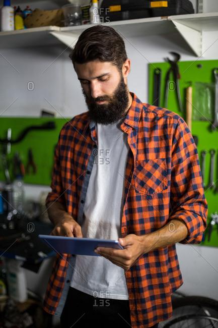Bike mechanic using tablet computer in bike repair shop