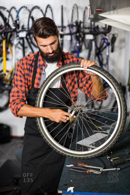 Hipster bike mechanic holding a bike wheel in bike repair shop