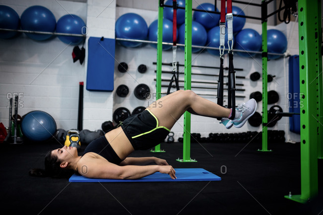 Woman doing suspension training with fitness straps at gym