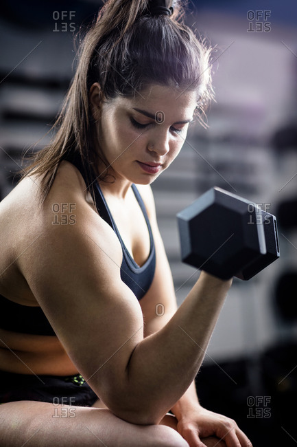 Woman exercise with dumbbells and working on her biceps at gym
