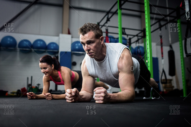 Man and a woman performing plank exercise at gym