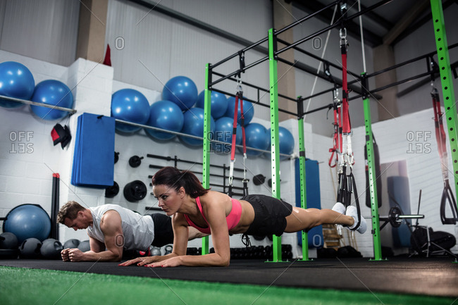 Man and woman doing suspension training with fitness straps at gym