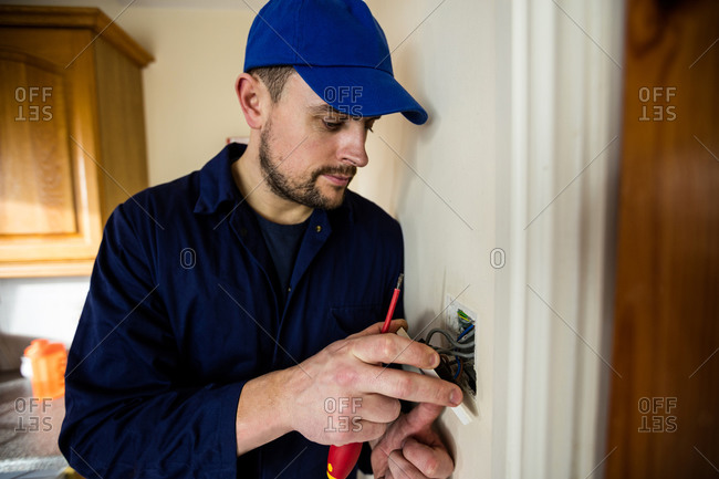 Electrician fixing a door bell at home