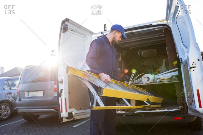 Handyman loading a ladder into a van