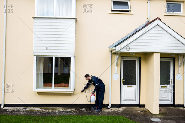Pest control man spraying pesticide outside the house