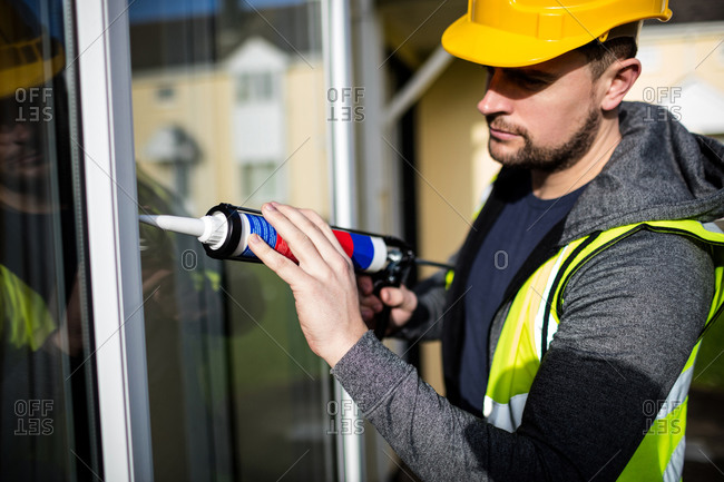 Pest control man using pest control injection outside the house