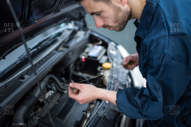 Mechanic checking the oil level in a car engine with a dipstick at the repair garage