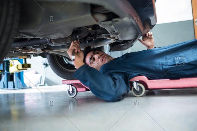 Portrait of mechanic repairing a car at the repair garage
