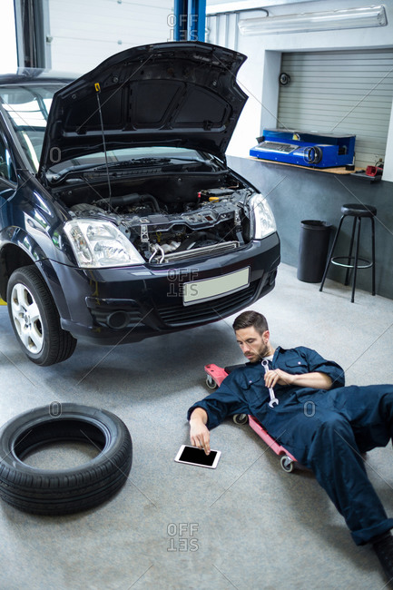 Mechanic using digital tablet while repairing a car at the repair garage