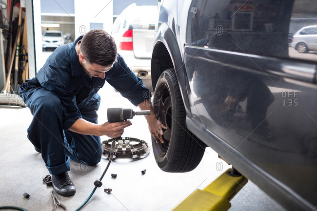 Mechanic changing car wheel with pneumatic wrench at the repair garage
