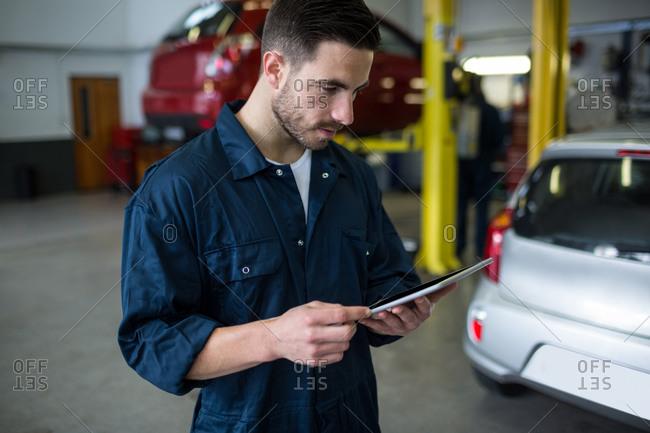 Mechanic using digital tablet at the repair garage