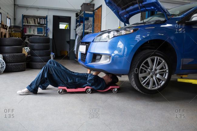 Female mechanic repairing a car at the repair garage