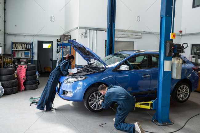 Mechanics examining a car engine and fixing wheel with pneumatic wrench at the repair garage