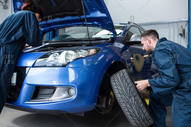 Mechanics examining a car engine and fixing wheel at the repair garage