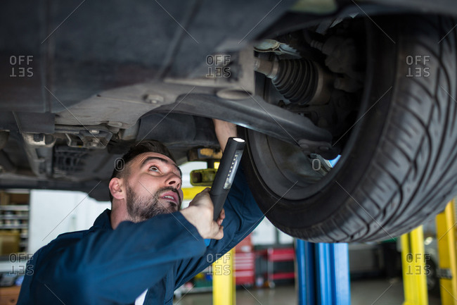 Mechanic examining car tire using flashlight at the repair garage