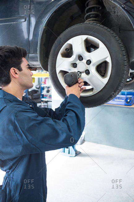 Mechanic fixing a car wheel with pneumatic wrench at the repair garage