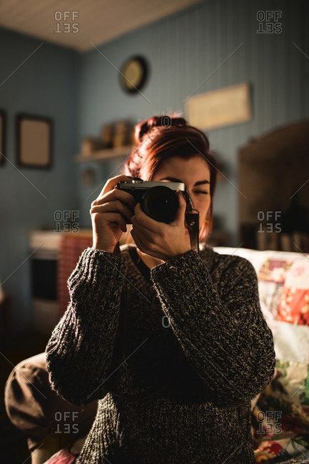 Young woman taking a picture with her camera at home