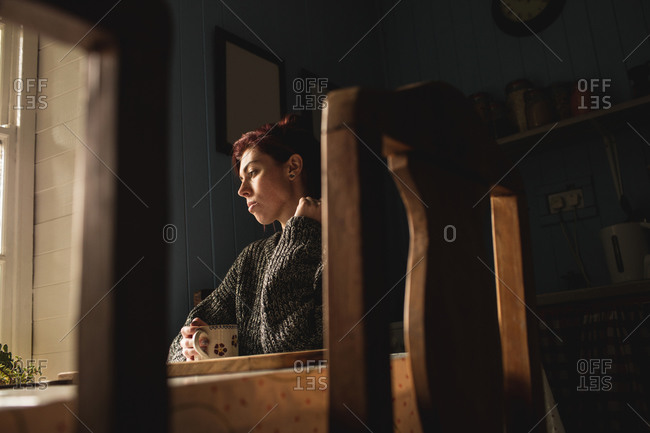 Thoughtful young woman sitting at table holding a coffee mug