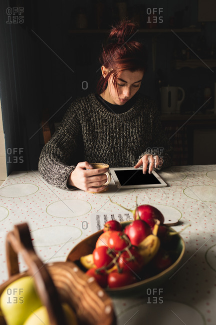 Young woman holding coffee mug and using digital tablet at home